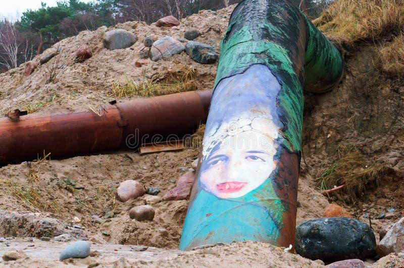 I graffiti su un tubo arrugginito, il fronte della ragazza hanno dipinto sul tubo fotografia stock