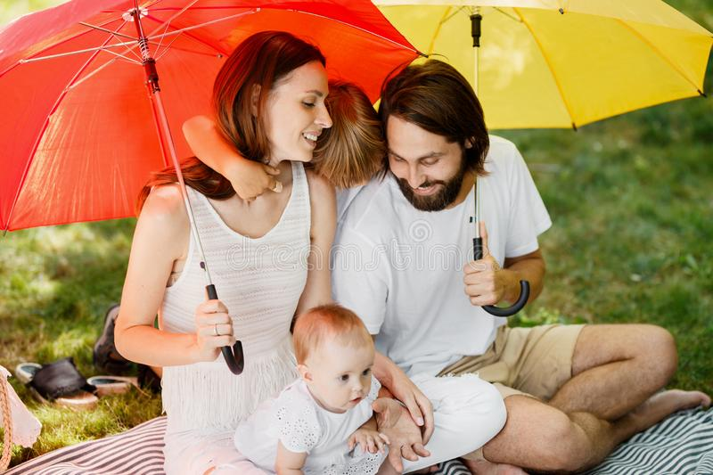 I grandi ombrelli luminosi coprono la famiglia felice vestita nei vestiti bianchi che si siedono sulla coperta dal sole fotografia stock
