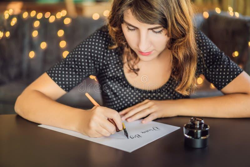 I grandi scopi di sogno dell'insieme agiscono Il calligrafo Young Woman scrive la frase su Libro Bianco Iscrivendo ornamentale de immagini stock