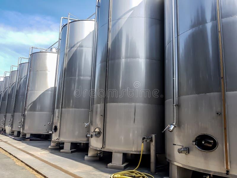I grandi serbatoi metallici per la produzione di vino, stoccaggio dei liquidi nei grandi volumi sono allineati immagini stock libere da diritti