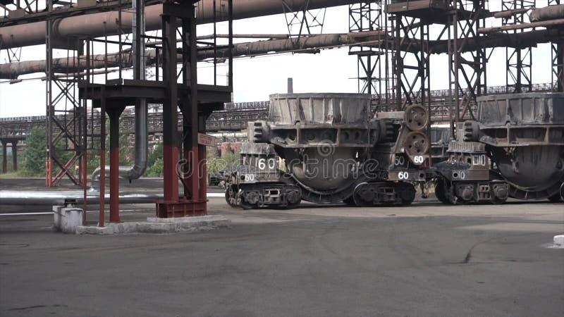 I grandi tini del metallo si sono mossi sui carretti all'aperto nella pianta metallurgica Metraggio di riserva Ferro e fabbrica e fotografie stock