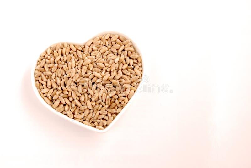 I grani del grano si trovano in un piatto in forma di cuore Copi lo spazio immagini stock
