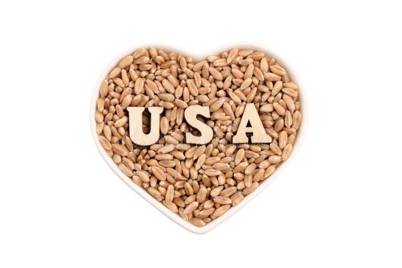 I grani del grano si trovano in un piatto in forma di cuore U.S.A. dalle lettere di legno sul grano Isolato su bianco Il concetto immagini stock