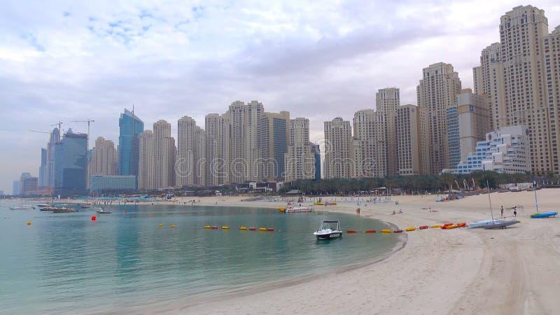 I grattacieli alti di un paesaggio urbano moderno e metropolitano torreggiano una bella, spiaggia bianca e sabbiosa un giorno cal immagini stock