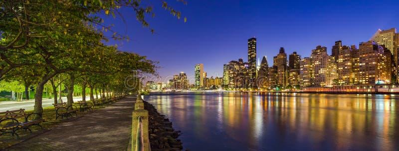 I grattacieli di Manhattan di Midtown ed il East River a penombra da Roosevelt Island passeggiano di estate New York City fotografia stock libera da diritti