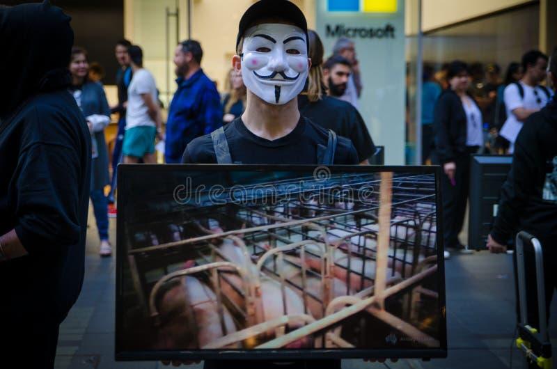 I gruppi di persone messi sulla maschera anonima e tengono il monitor dello schermo per dividere le informazioni su crudeltà dell immagini stock