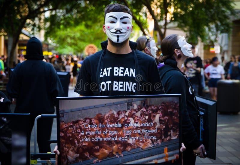 I gruppi di persone messi sulla maschera anonima e tengono il monitor dello schermo per dividere le informazioni su crudeltà dell immagine stock