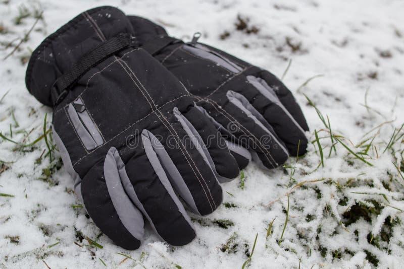 I guanti dell'inverno nella neve, guanti neri di sport si trovano nell'inverno nella neve fotografia stock