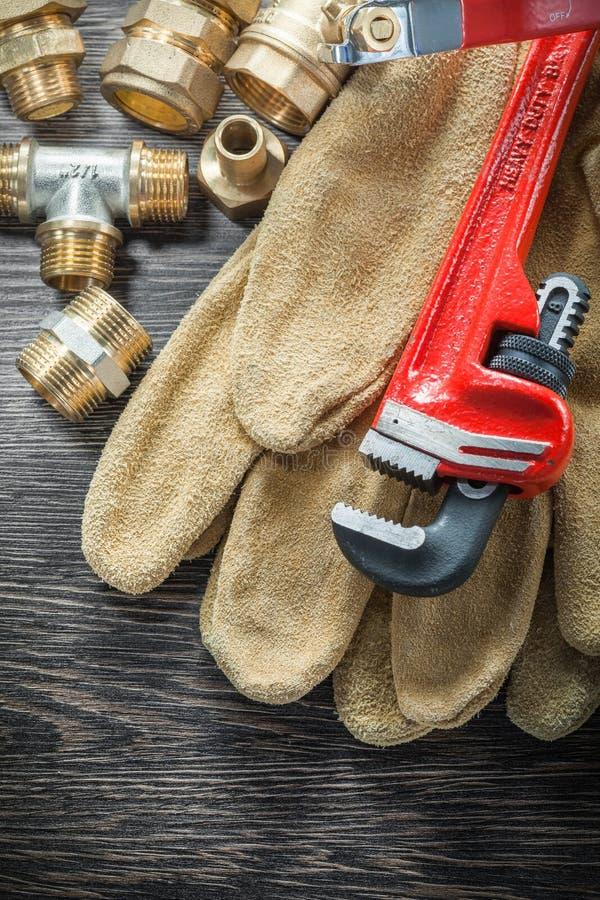 I guanti protettivi dei connettori del tubo della chiave inglese dell'impianto idraulico innaffiano la v fotografie stock libere da diritti