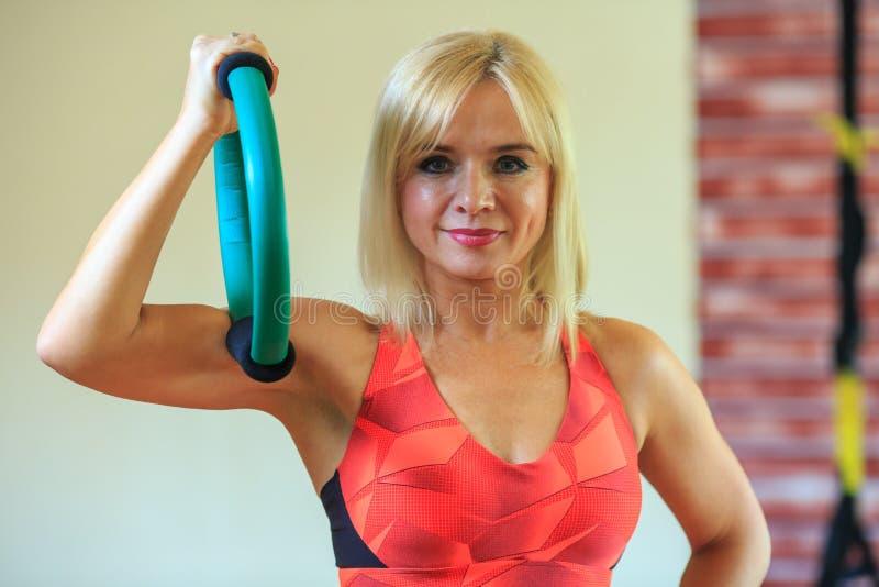 I halvfigur portrai av en härlig mogen blond kvinna i ljus orange träningsoverall med en expander i hennes hand i en konditionmit arkivfoton