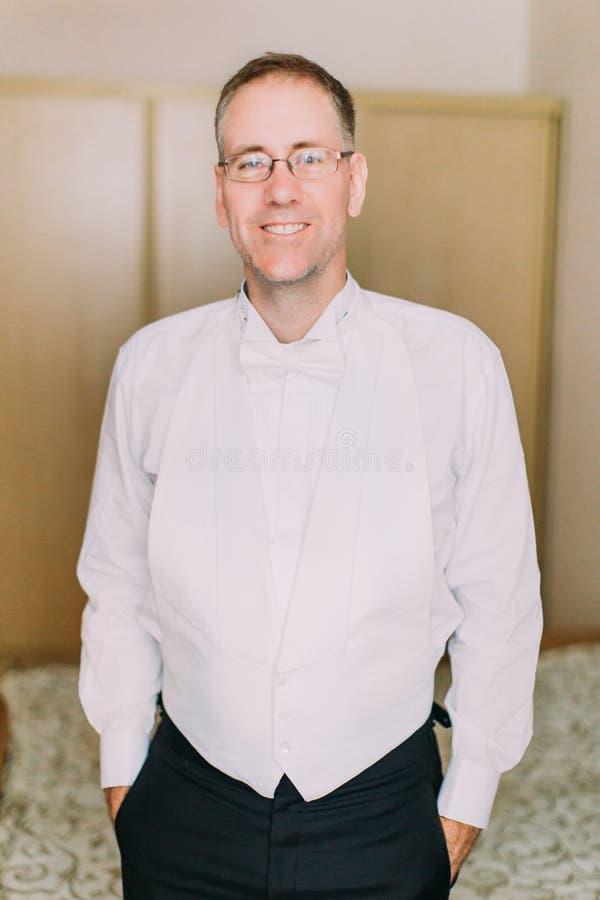 I halvfigur stående av de charmiga le bärande exponeringsglasen för brudgum royaltyfri fotografi