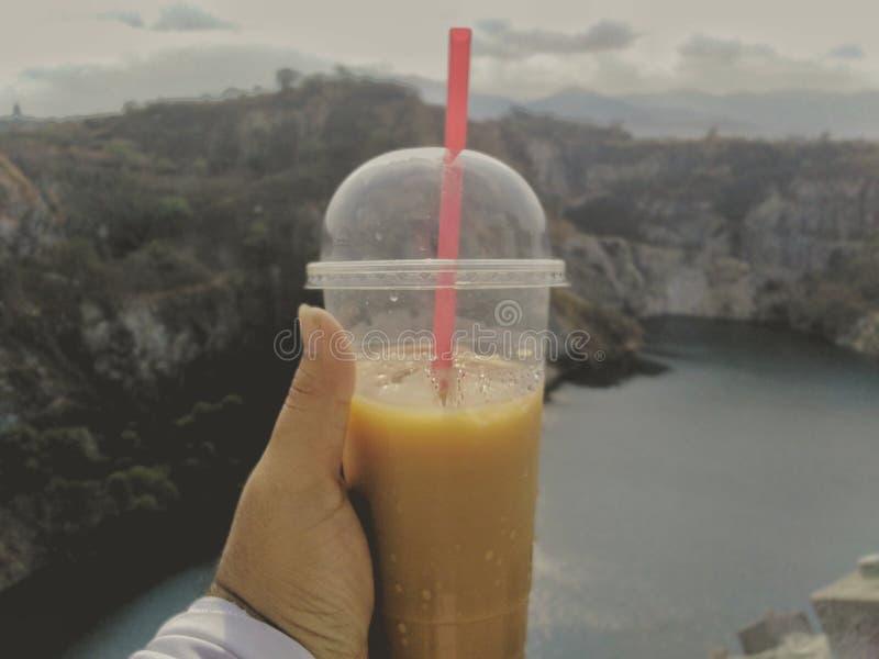 I handen som rymmer ett kaffe, råna med en härlig sikt royaltyfria bilder