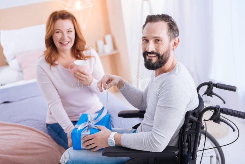 Inspired crippled man smiling and opening a gift. I am happy. Bearded disabled men smiling and opening a present while sitting in a wheelchair and a smiling royalty free stock photos