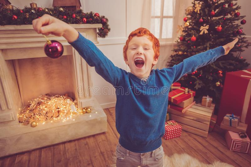 Overjoyed ginger-haired boy shouting while holding Christmas ball stock images