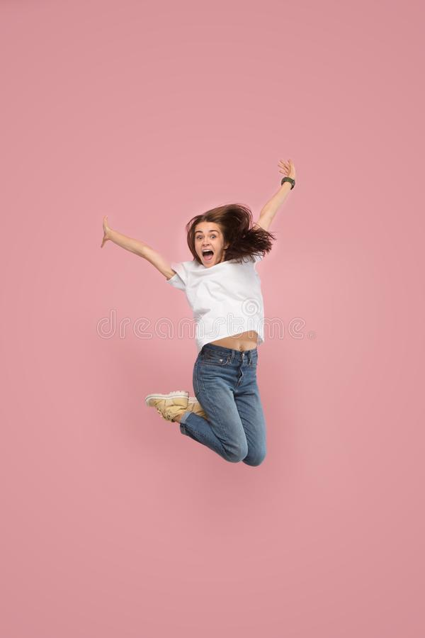 Freedom in moving. Pretty young woman jumping against pink background stock images