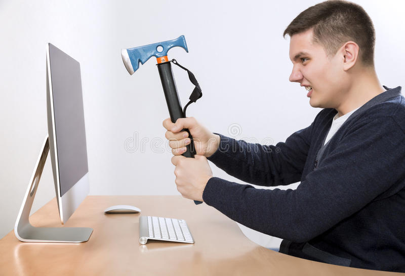 I hate this job Crazy man is going to destroy his. Crazy man is going destroy his computer desktop with iron axe threatening it as hummer into big screen smart royalty free stock image