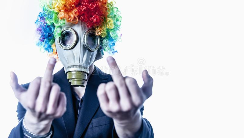 I hate my office work. Office employee clown in suit in the gas. Mask showing middle finger gesture as a symbol of protest against low wages, overtime working stock photo
