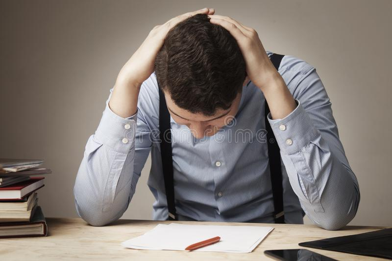 I hate my office work. Young businessman working with documents. stock image