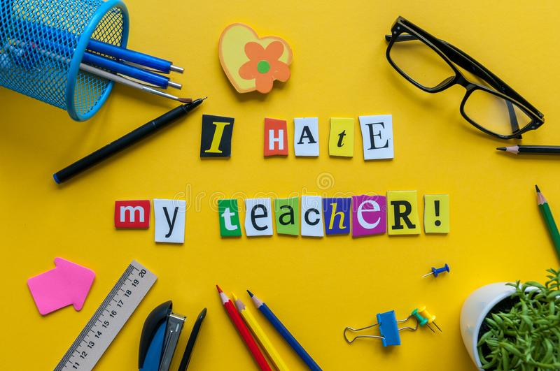 I hate my Teacher - text made with carved letters on yellow desk with office or school supplies on pupil table.  stock photography