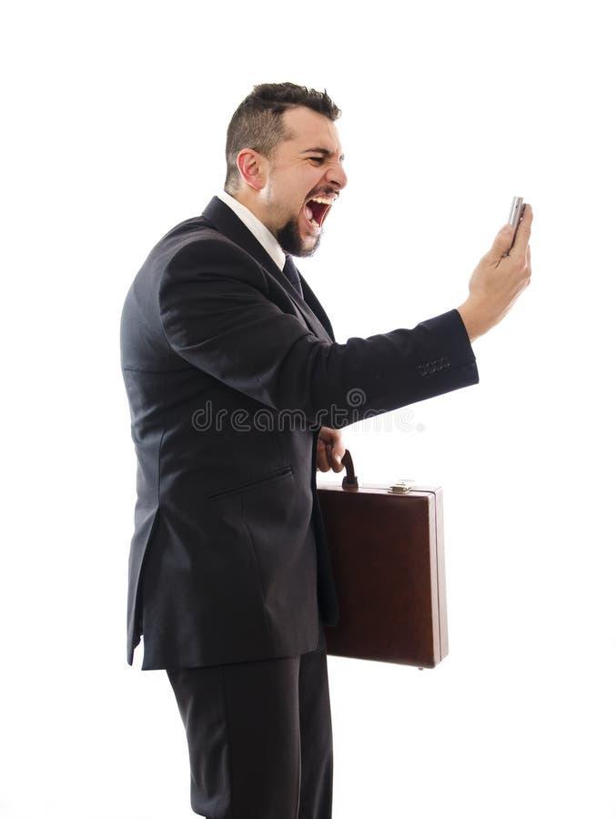 I hate phones!. Agressive businessman shouting phone on white background stock image