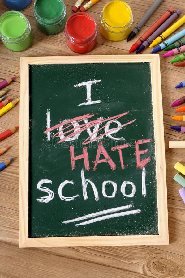 I hate school, back to school concept written on blackboard. The words I Hate School written on a small elementary blackboard with various paints, crayons and royalty free stock image