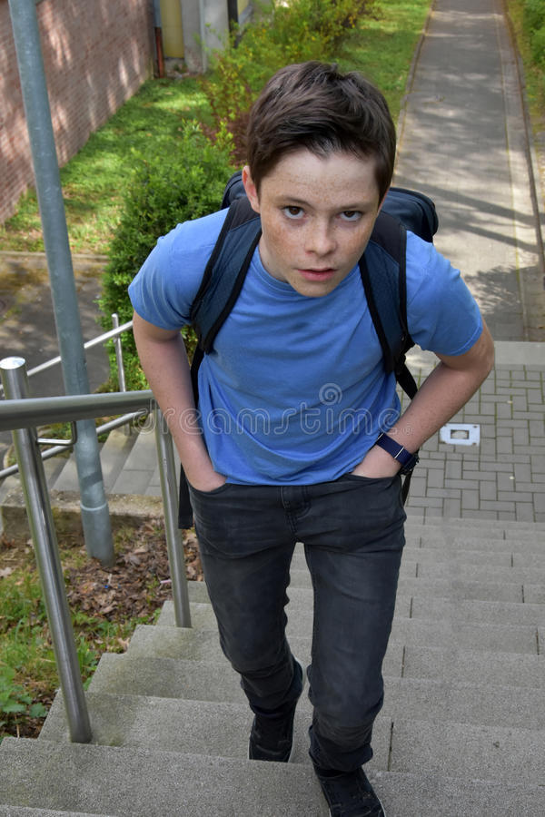 I hate the school. Boy on his way to school, he looks not very happy stock photos