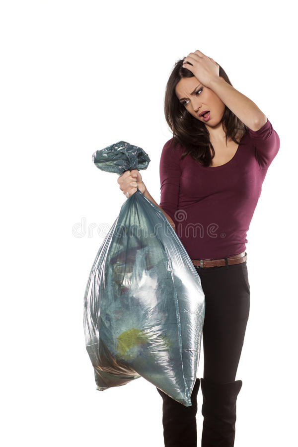 I hate throwing out the garbage. Unhappy young woman holding a full garbage bag on white background stock image