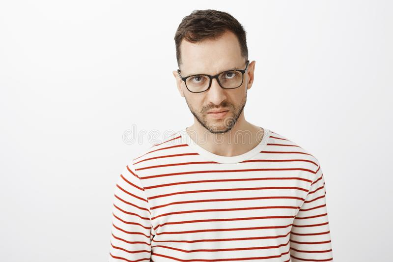 I hate you. Portrait of off angry adult european who expressing disdain and anger, looking from under forehead stock photo