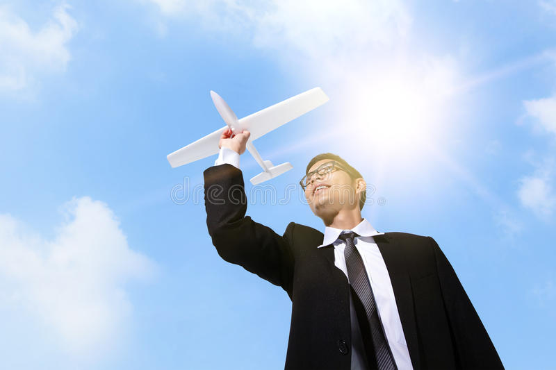 I have a dream. Businessman holding airplane with sky background, asian stock photography