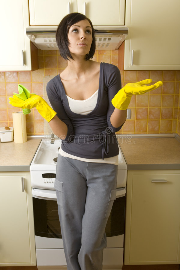 I have enough houseworks. Young woman in yellow rubber gloves. She's standing back at cooker with raised hands. She's looking up. Front view stock photo