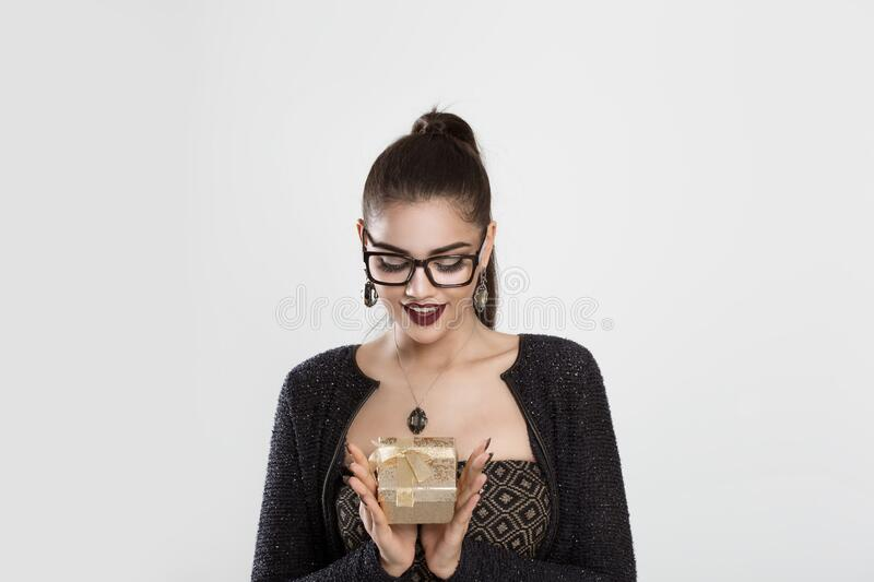 I have a gift. Woman tan girl in eye glasses holding gift in han royalty free stock photos