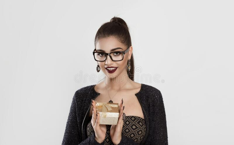 I have a gift for you. Woman in eye glasses holding gift in hand looking at you camera happy smiling Fashion tan girl ponytail stock photo