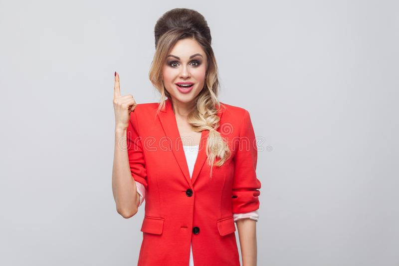 I have an idea. Portrait of excited beautiful business lady with hairstyle and makeup in red fancy blazer, standing and looking at. Camera with surprised face royalty free stock photos