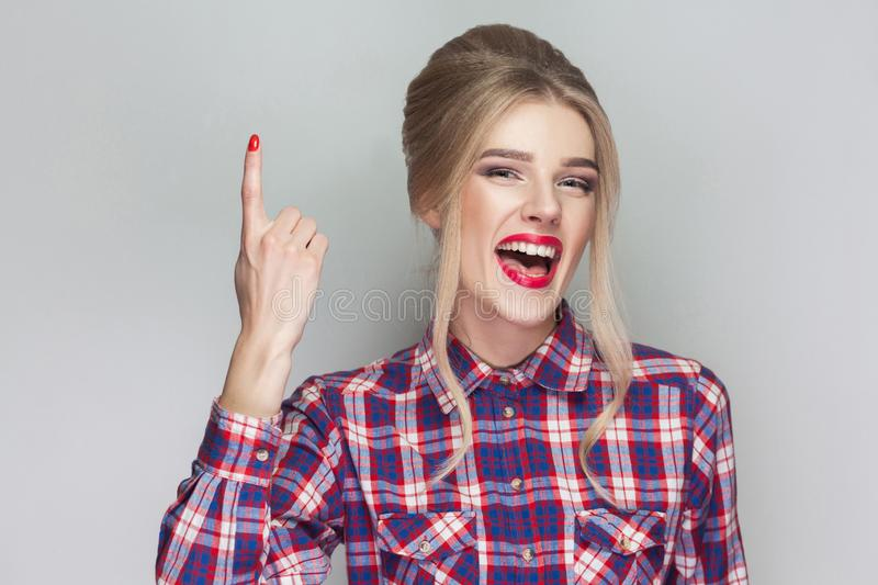 I have a idea. Satisfied beautiful girl with pink checkered shirt, collected updo hairstyle and makeup standing looking at camera royalty free stock photos