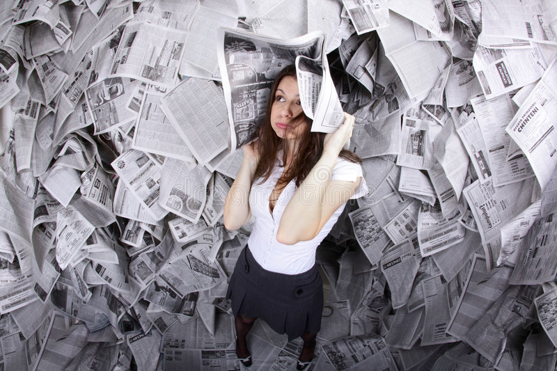 I have news for you. Business woman surrounded by newspapers everywhere and with a newspaper over her head royalty free stock image