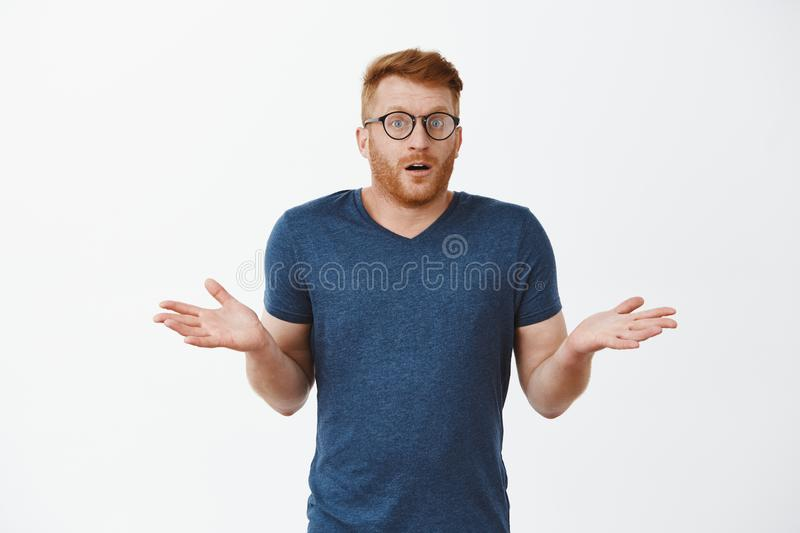 I have no idea how that happened. Portrait of clueless cute masculine male with red hair in glasses and t-shirt. Shrugging with spread palms and gazing stock photo