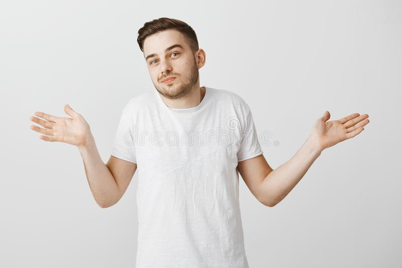 I have no idea man ask anyone else. Careless relaxed handsome unshaven guy with stylish haircut in white t-shirt making. Shoulder shrug gesture with palms royalty free stock photography