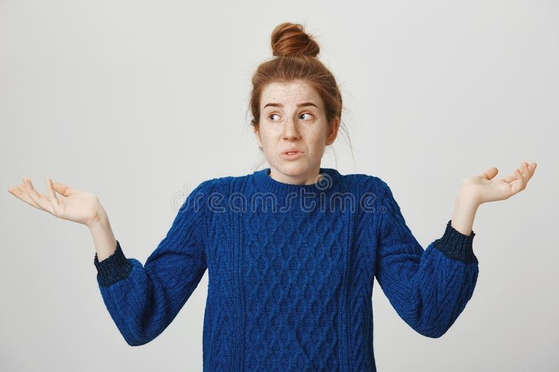 I have no idea, it was not my fault. Portrait of confused and troubled cute redhead woman in winter sweater shrugging royalty free stock photography