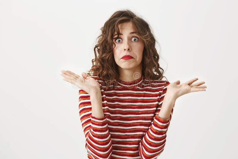 I have no idea what happened. Confused female with curls and in striped cropped top raising palms in clueless or puzzled royalty free stock photo