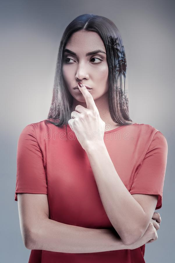 Attentive young woman covering her mouth. I have plan. Attractive female person holding arms on chest and looking aside while creating new plan royalty free stock images