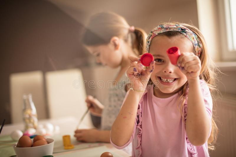 I have something for an Easter bunny. Little girls coloring Easter egg royalty free stock image