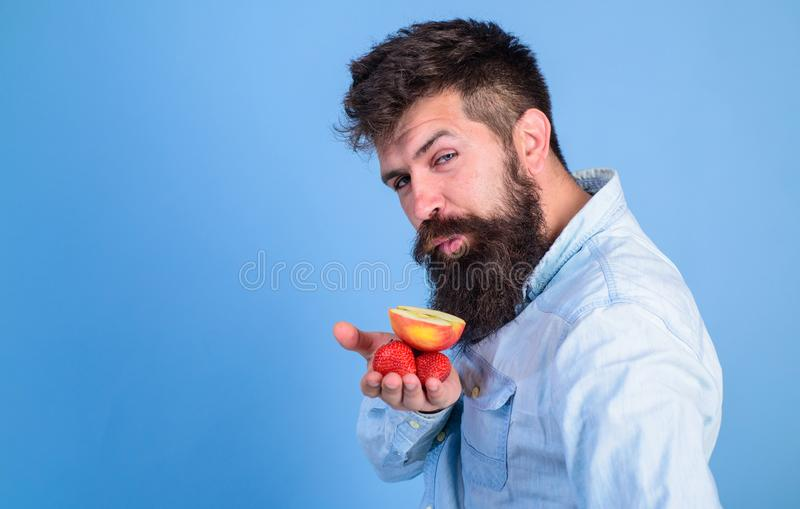 I have treats for you. Hipster bearded holds strawberries and apple on palm. Man cunning face with beard offers organic royalty free stock photography