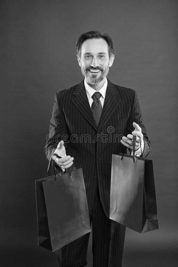 I help economy, I shop a lot. Happy shopper red background. Businessman hold shopping bags. Mature man enjoy shopping stock photos