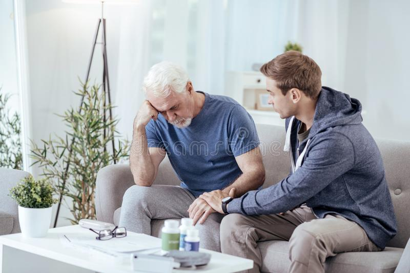 Worried male caregiver calming down senior man royalty free stock photos