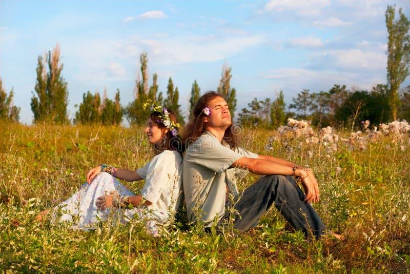I hippy delle coppie si siedono nell'erba immagini stock libere da diritti