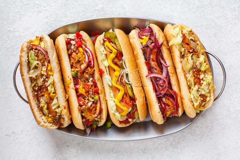 I hot dog completamente hanno caricato con le guarnizioni assortite su un vassoio immagini stock libere da diritti