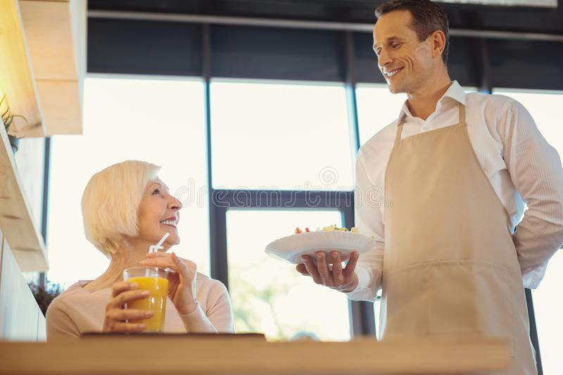 Positive aged woman waiting for her breakfast stock photography