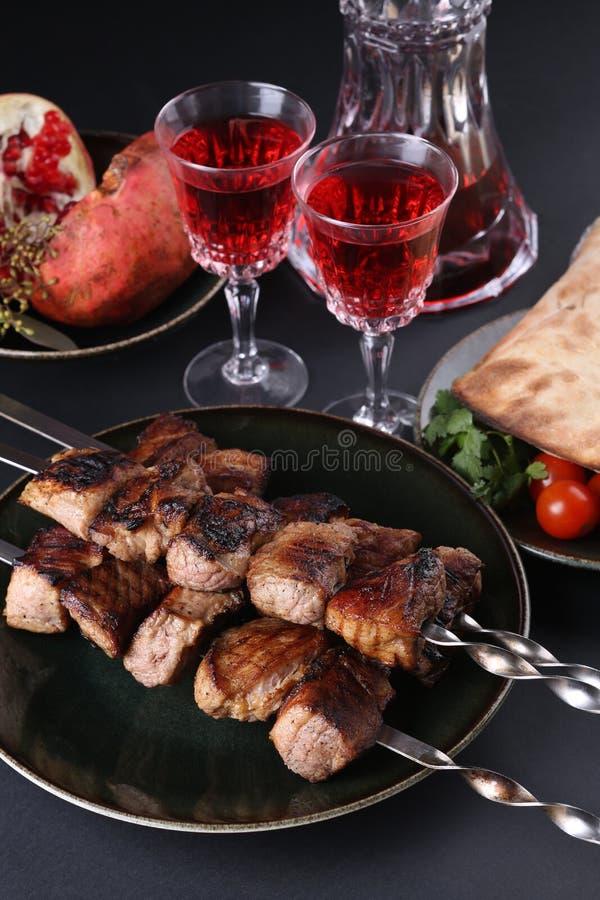 I kebab arrostiti col barbecue sani della carne di maiale cubati magra sono servito con il pomodoro, la pita, i verdi, il granato fotografia stock libera da diritti