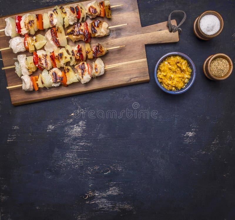 I kebab arrostiti con i peperoni, la carne di maiale e l'ananas su una salsa del tagliere ed i condimenti confinano il posto per  immagini stock libere da diritti