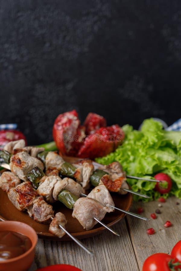 I kebab delicati appetitosi di carne di maiale sugli spiedi hanno allineato con un piatto degli ortaggi freschi e del melograno m immagine stock libera da diritti